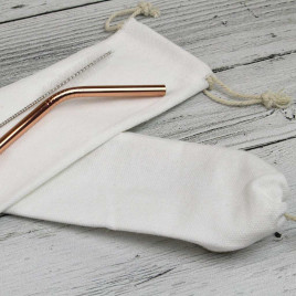 White cloth bag with rose gold stainless steel reusable straw and brush