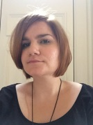 Kirsty, a white woman, with short hair is looking at the camera. She is wearing a black top.