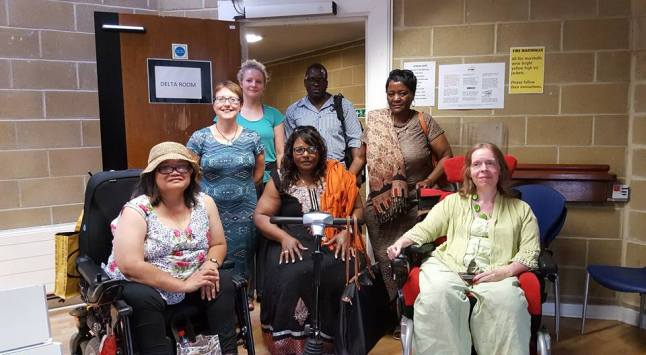6 women, 1 man in group photo, 2 women in wheelchairs and one in a scooter.