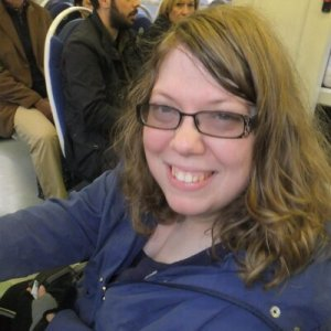 Zara, a white woman, is smiling at the camera. she has black rimmed glasses on