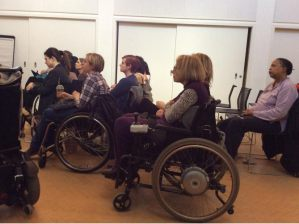 about eleven/twelve women looking/listening intently. some are wheelchair users.