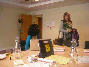 2 women, one looking away with her laptop in conversation with the other. There is a portable hearing loop on the table as well as bottles of water
