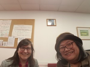 two women, one white and the other East Asian, both with glasses smiling at the camera.