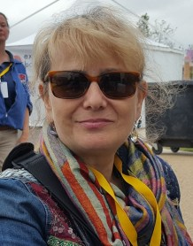 white woman with hair tied back and sun glasses. she has a colourful scarf.