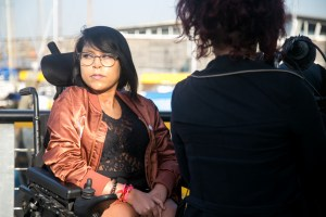 young Asian woman in a leather jacket being filmed