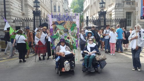 Group of women, 2 wheelchair users, with a colourful textile banner saying 'Sisters of Frida' Hear the voices