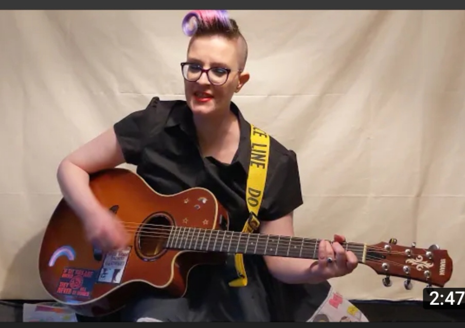 white woman with punish hair playing a guitar