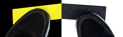 Dos cintas antideslizantes pegadas al suelo, una amarilla y una negra con zapatos encima