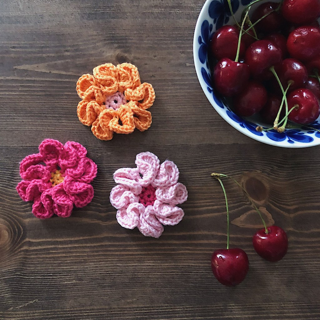 Three highly textured little flowers is placed on a dark wooden table together with a bowl of cherries