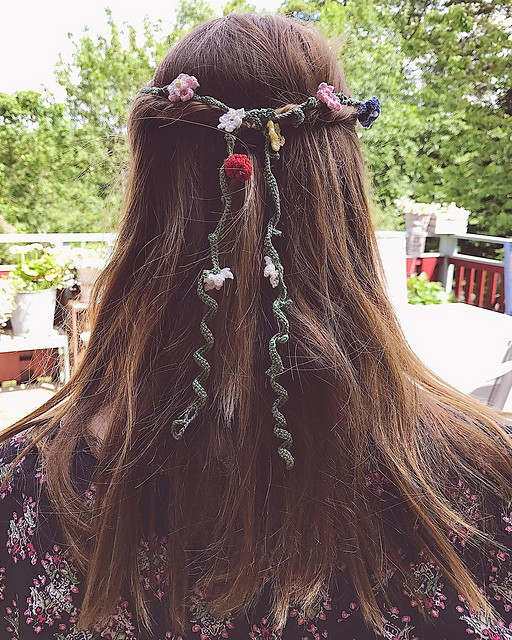 A closeup of Tess hair with the midsummer seven floral head band tied around her he'd