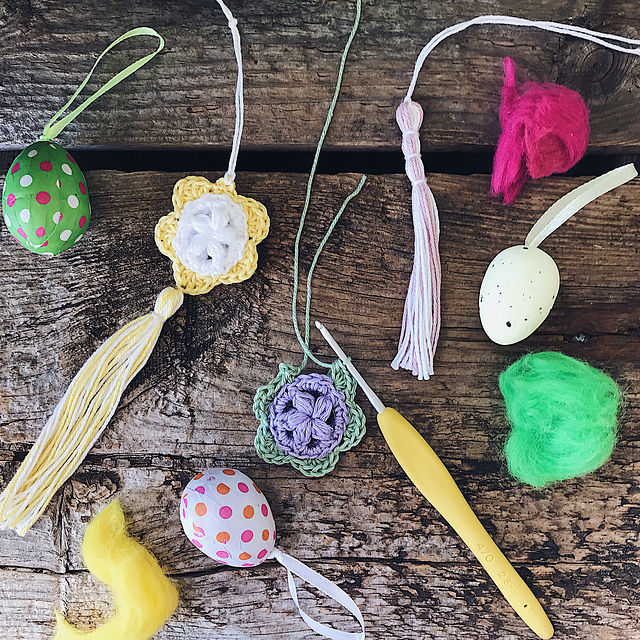 Two Puffy Easter Medallions are placed on a dark wooden backdrop tighter with tassels, a crochet hook and small Easter paper eggs