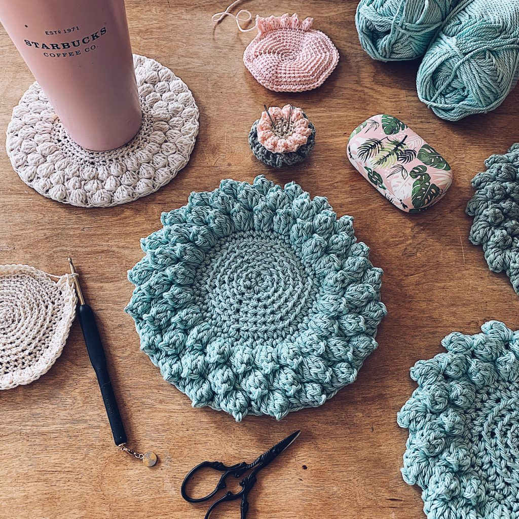 A flatlay picture of the Pop around the plate crochet coaster in different shades of teal, beige and pinks