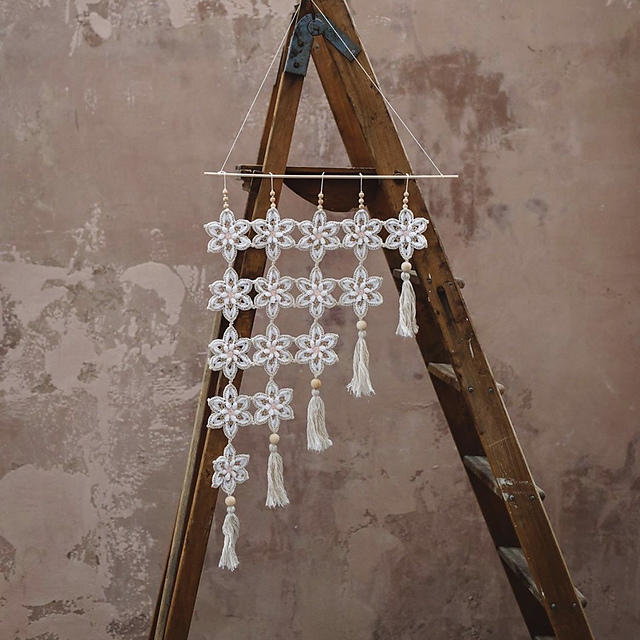 A crocheted floral wallhanging hung from an vintage ladder infant of a terracotta brushed wall
