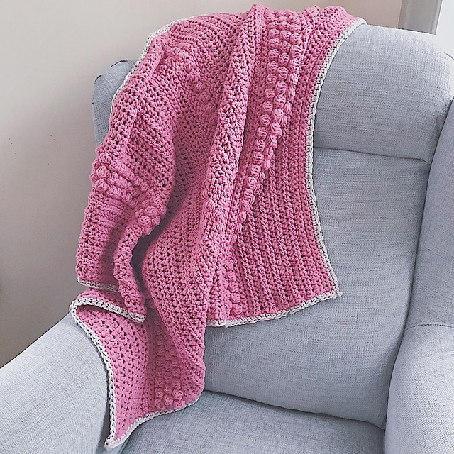 A pink Oh How I Love This Throw with a light grey boarder is draped over a light blue armchair