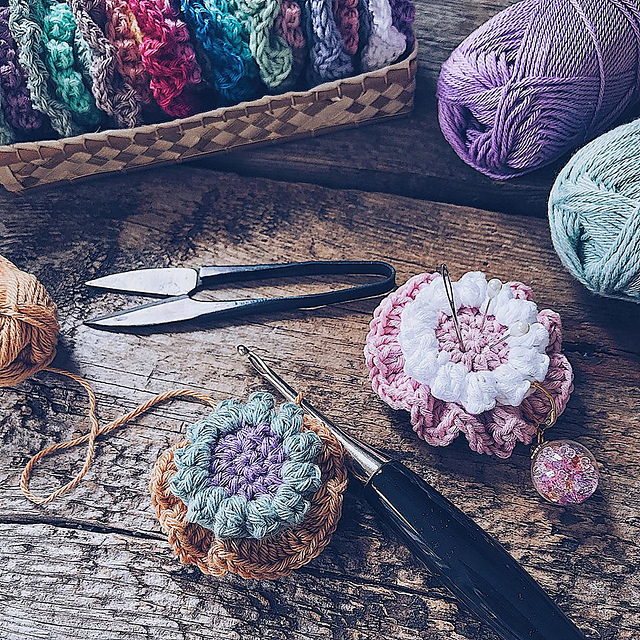 Two Ruffle Puff Pincushions are placed on a wooden backdrop with yarn skeins and crochet tools in dark colors