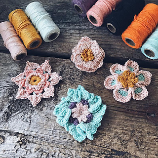 A flatlay with Silk Yarn spools and crocheted flowers placed on a wooden backdrop