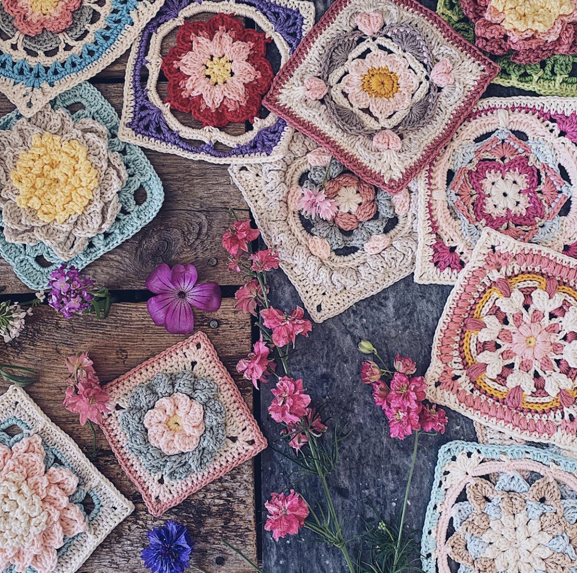 A flatlay picture of beautiful textured granny squares and picked flowers in lots of different colors