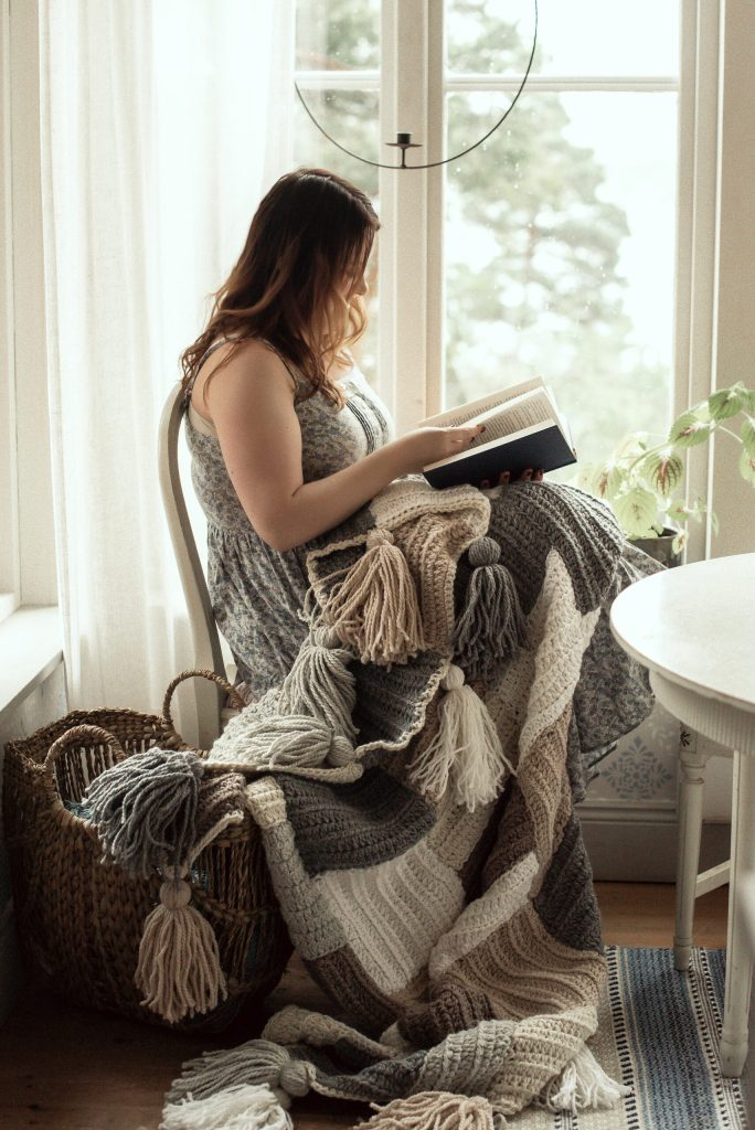 Tess sitting in her kitchen reading a book with the Stay Awhile Boho Blanket draping over her lap and down on the floor