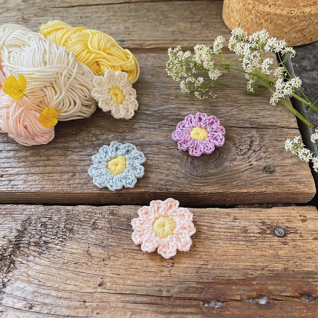 Three Butter Bloom Flower in three colors placed on a wooden background together with yarn skeins and fresh flowers