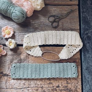 Two crocheted headbands are placed on a wooden backdrop together with some pastel coloured yarn and flowers
