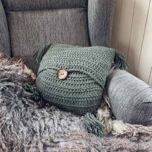 A moss green Stay A While Boho Pillow with a large wooden centre button placed in a dark grey arm chair onto of a long haired grey sheepskin