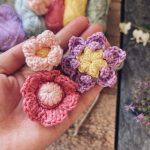 A closeup of three small crocheted flowers in the palm of Tess with yarns in the background