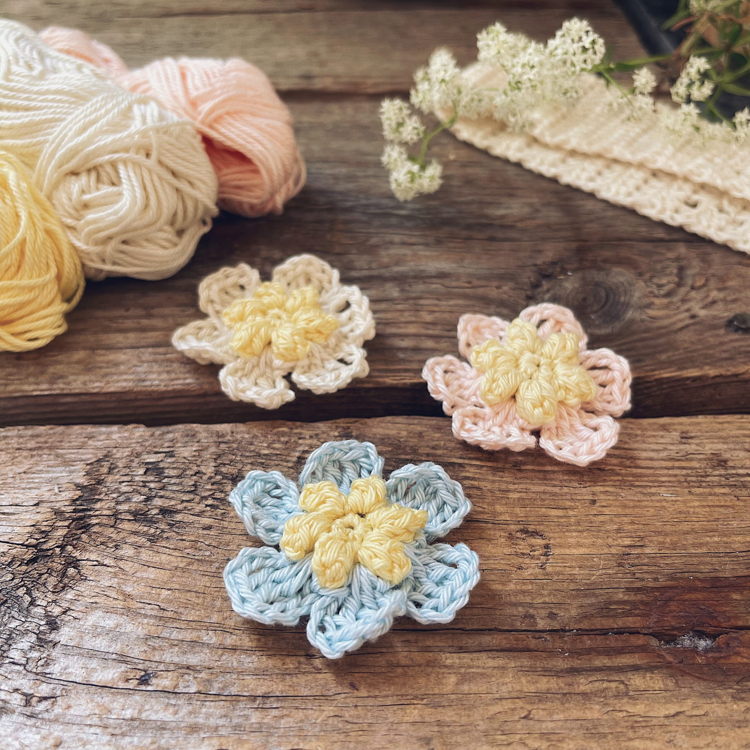 The Pop Drop Flower in three colors placed on a wooden background together with yarn skeins, fresh flowers and a cream coloured Forver Love Headband