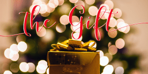 """""""The Gift"""" in red script, golden present wrapped with Christmas tree behind it"""
