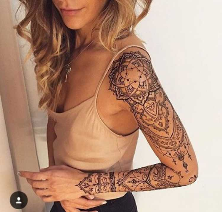 Mulher com o braço todo tatuado