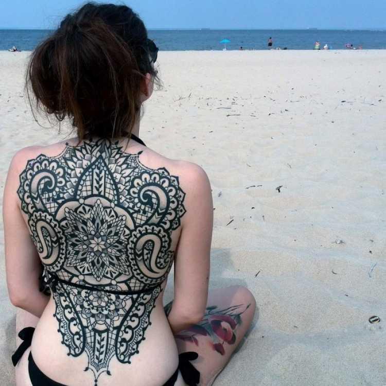 Mulher com tatuagem nas costas