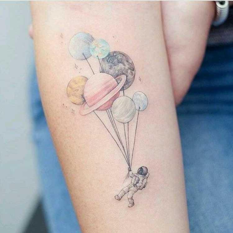 Tatuagem com imagem de astronauta e planetas