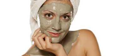 Mulher aplicando a máscara caseira e natural de argila, pepino e iogurte para tratar a pele oleosa