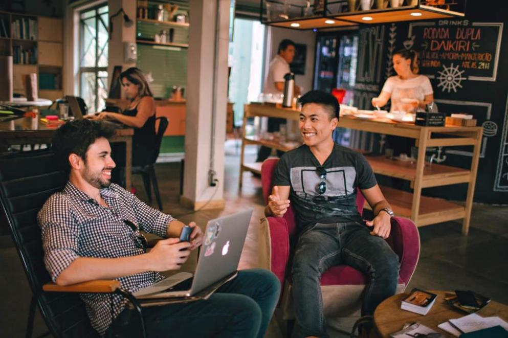 happy co-workers sitting with laptops on comfy chairs