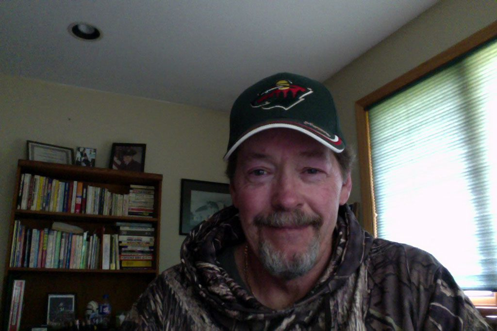 Dan happily working from home, dressed in his favorite baseball cap and sweater.