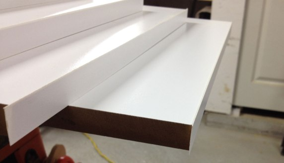 The closet bookshelf pieces with edge banding applied. Now to file off the excess