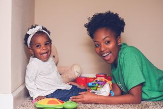 Adorable baby and sitter playing. Both are looking at camera smiling and laughing.