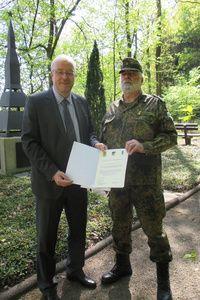 Das Foto zeigt Bürgermeister Walter Kiß und OFw d.R. Rainer Koch bei der Übergabe der Patenschaftsurkunde auf dem Friedhof in Eichen.