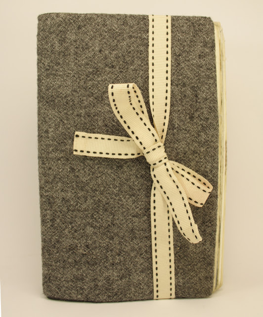 moleskine notebook covered in tweed trousers and ribbon