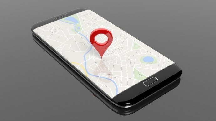 Smartphone with map and red pinpoint on screen, isolated on black background.