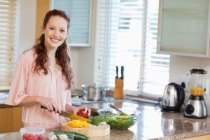 Smiling woman preparing salad