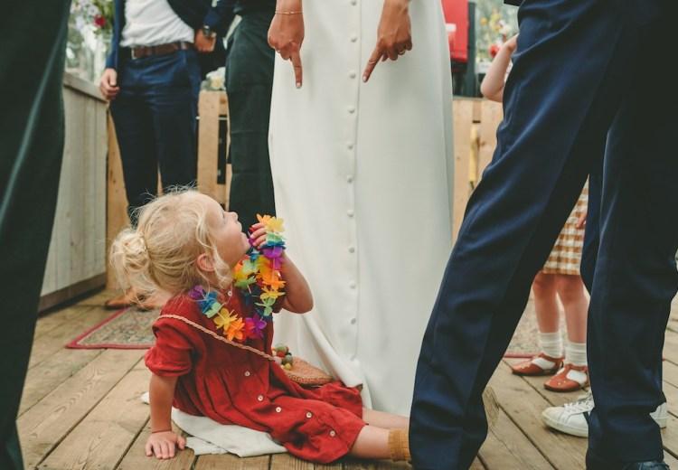 kind zittend op trouwjurk