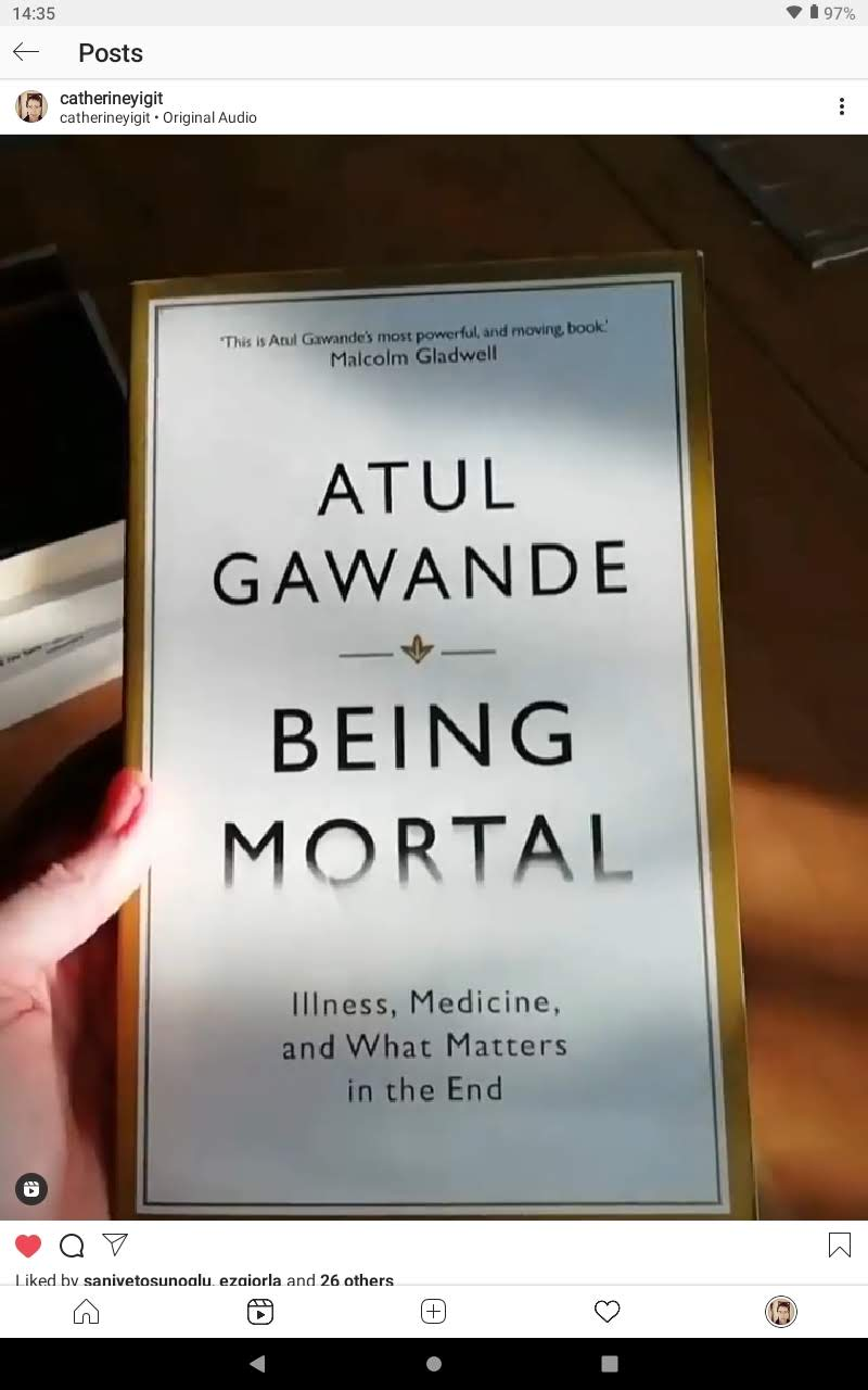 A hand holding a book called Being Mortal by Atul Gawande