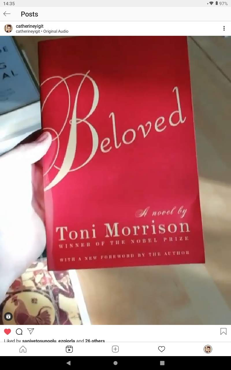 A hand holding the book Beloved by Toni Morrison