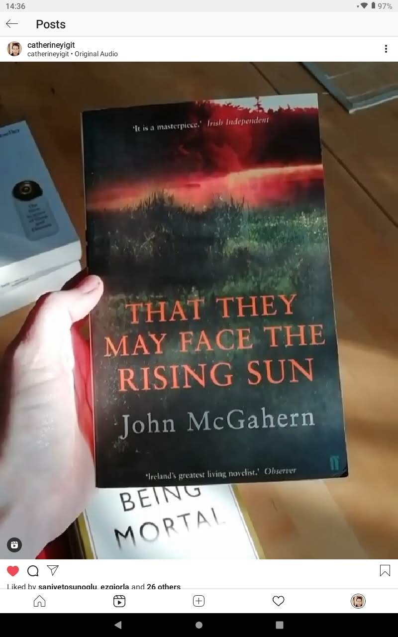 A hand holding a book called That They May Face the Rising Sun by John McGahern