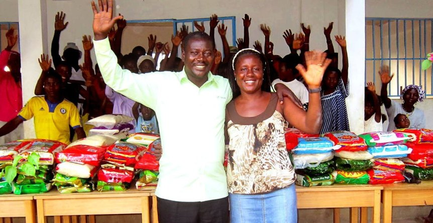 Aid workers smiling and waving with African villagers distributing food aid from Skanda Vale Ashram in the UK