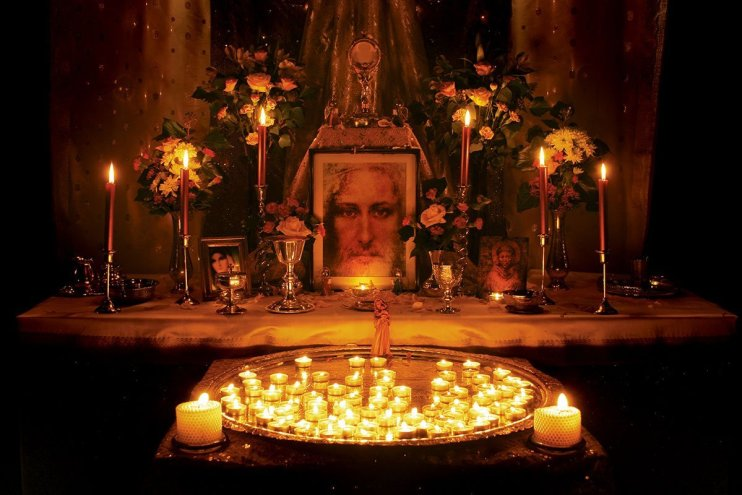 A Christian shrine with prayer candles and a picture of Jesus, in the Lord Murugan Temple at Skanda Vale