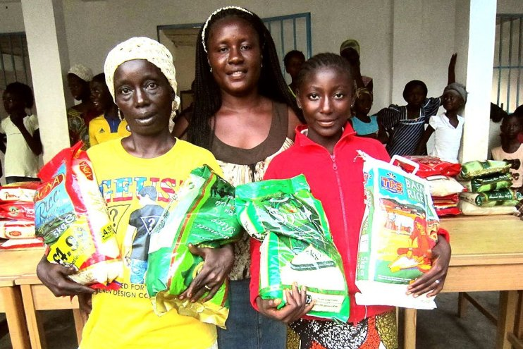 African people with bags of rice from Skanda Vale food aid programme