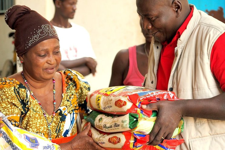 An aid worker distributing food aid with a smile