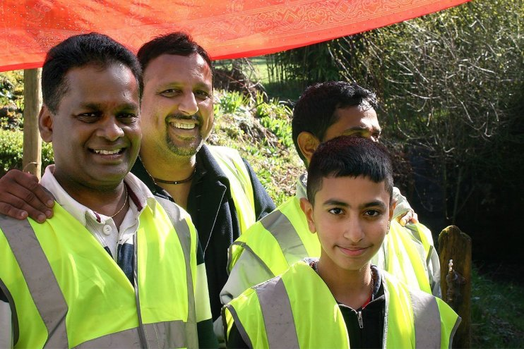 A group of devotees in high visibility jackets volunteer their services as seva at Skanda Vale Ashram in Wales