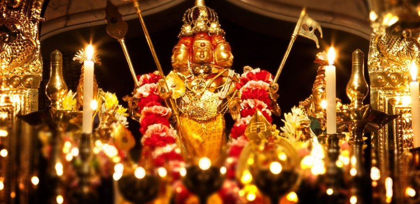 A close up image of Lord Murugan (also known as Lord Subramanium) with lamps and flower garland at the gopurum of the Murugan Temple at Skanda Vale Ashram in Wales.